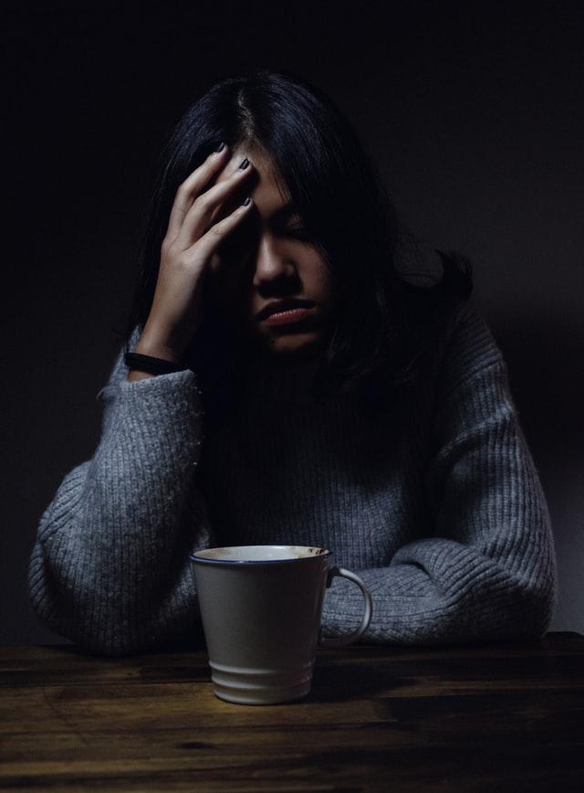 Woman in dark developing a self care plan