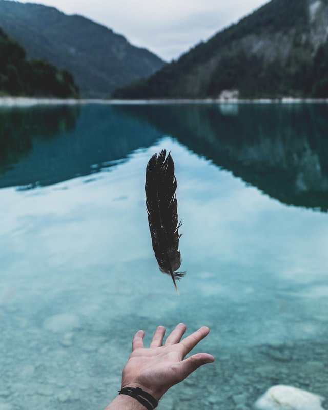 Man letting go of things to let go of a feather on a lake