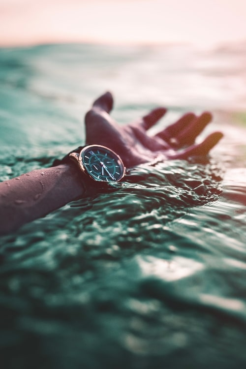 hand floating above water with watch on