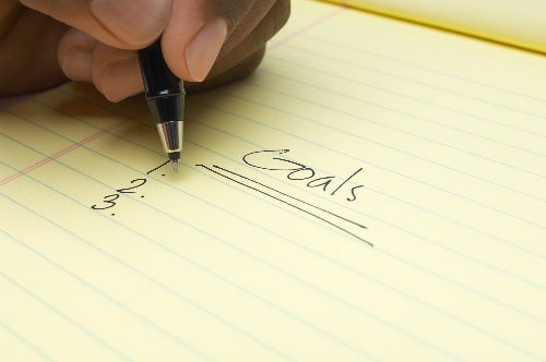 Person writing list of goals