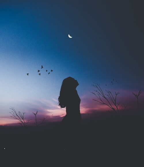 woman standing looking up to moon