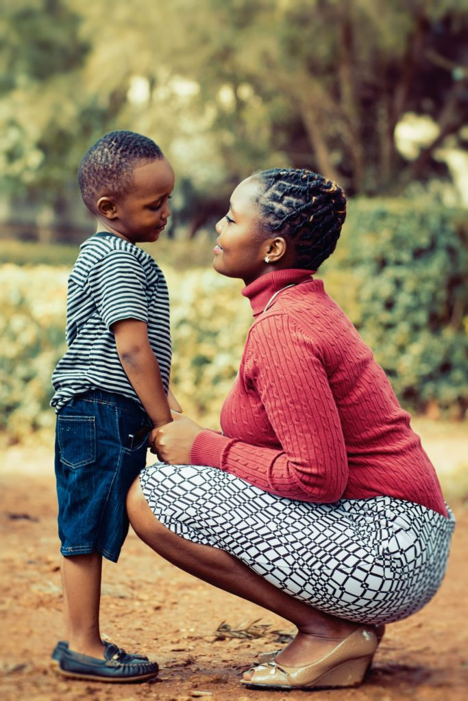 woman bending down smiling at her young son