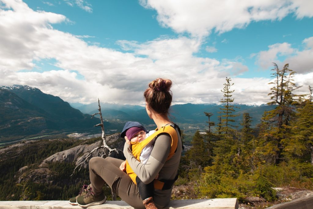 woman carrying baby on hike practicing self care and being less stressed