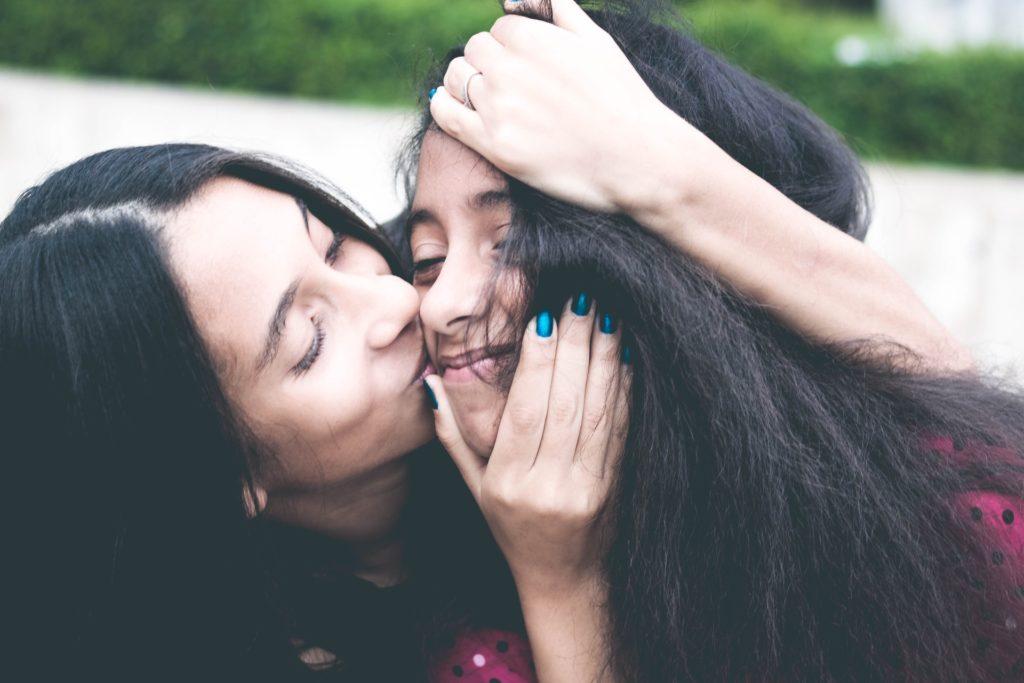 woman kissing cheek of her teenage daughter