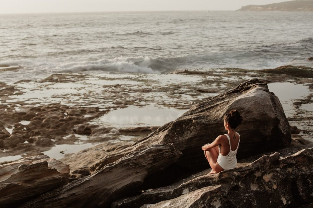 woman meditating on a rock near the ocean