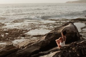 woman sitting on rock meditating