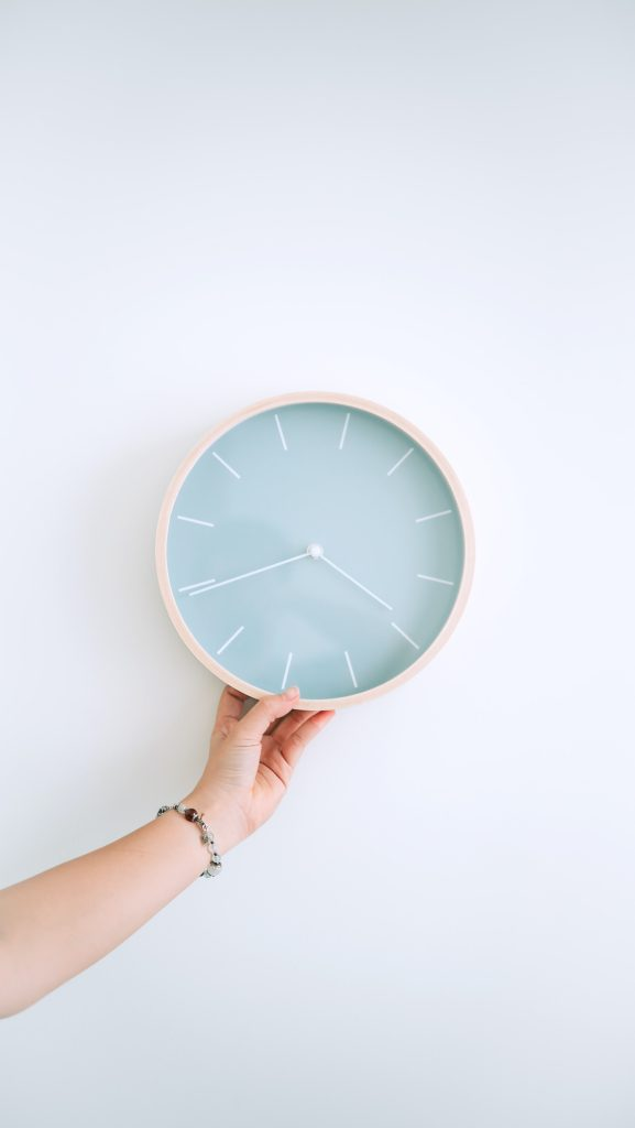 woman holding up a teal clock