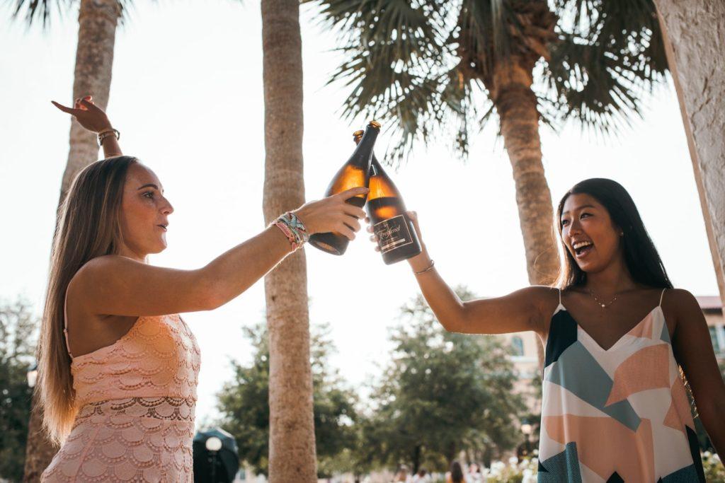 two friends drinking bottle of liquor
