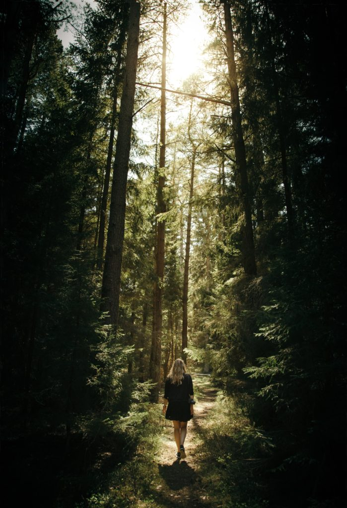 Woman walking through the forest practicing mindfullness
