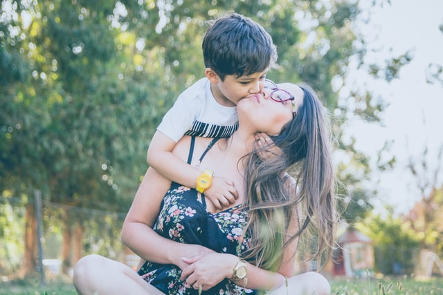 woman kissing her school age son