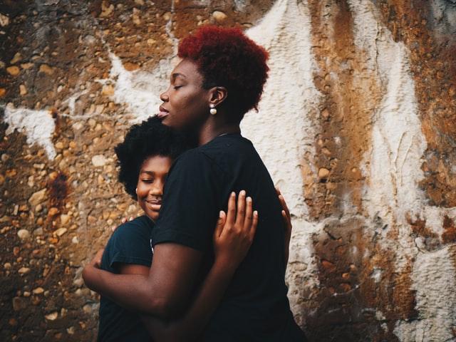 woman hugging her teenaged daughter