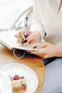 Woman writing developing a self care plan