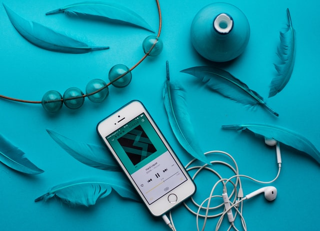 Cell phone playing music playlist on blue background