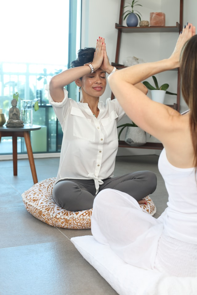 Women enjoying meditating together and the meditation benefits