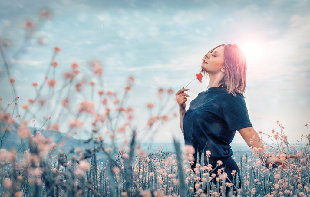 Woman walking through field of flowers