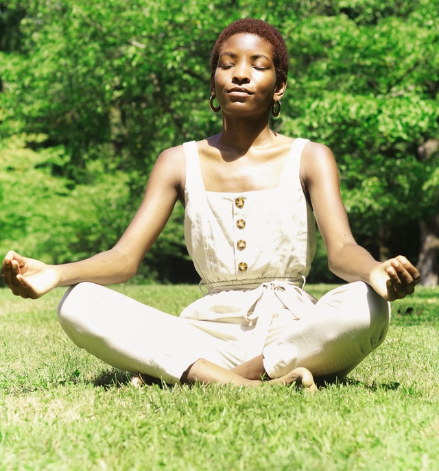 Woman practicing mantra meditation while sitting on the grass