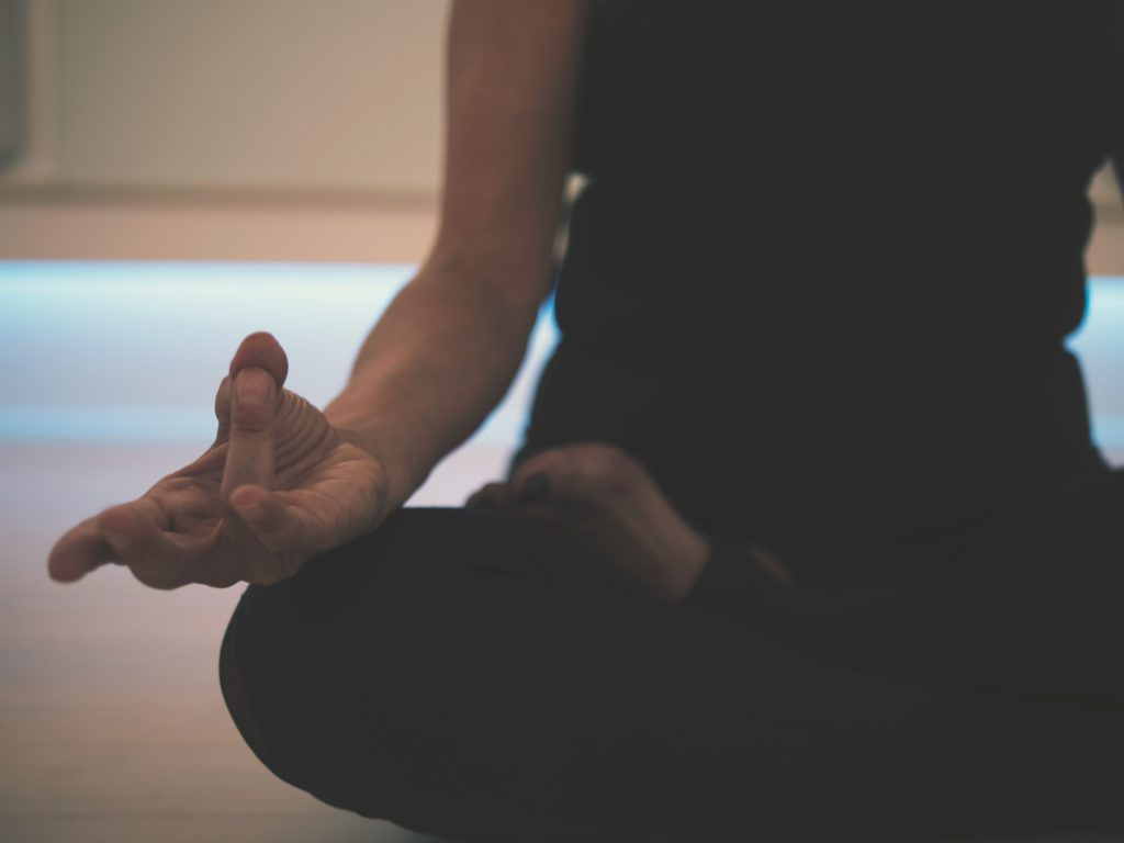 Person sitting on the floor meditating
