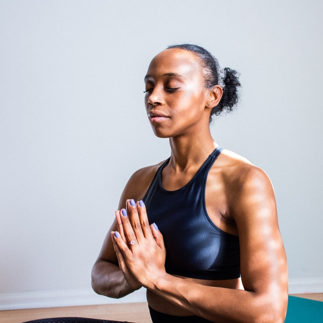 Woman meditating, practicing self care exercise