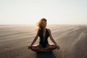 Woman meditating practicing self care and mental health