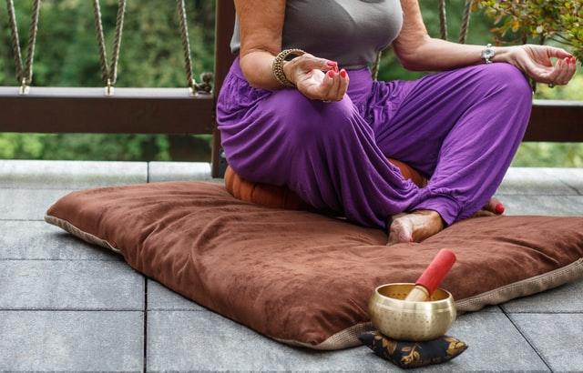 Woman sitting on pillow on ground meditating