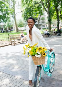 Woman pushing a bike with sunflowers